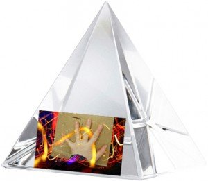 A crystal pyramid with a girls hand touching it.