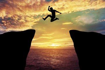 man jumping between rocks
