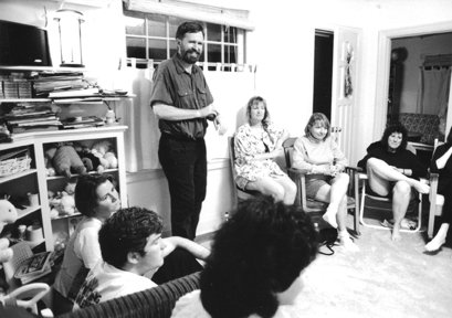 Alan Sheets standing in a house teaching people sitting in a circle