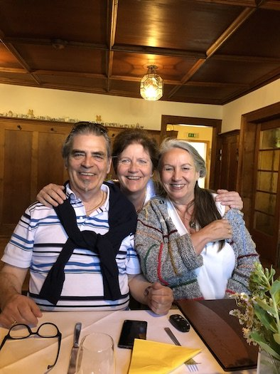 Siv Roland smiling with two people