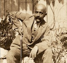 George Ivanovich Gurdjieff sitting and leaning on his cane