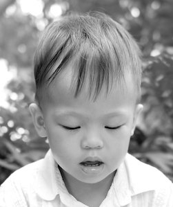 A 4 little boy with closed eyes and a deeply calm expression